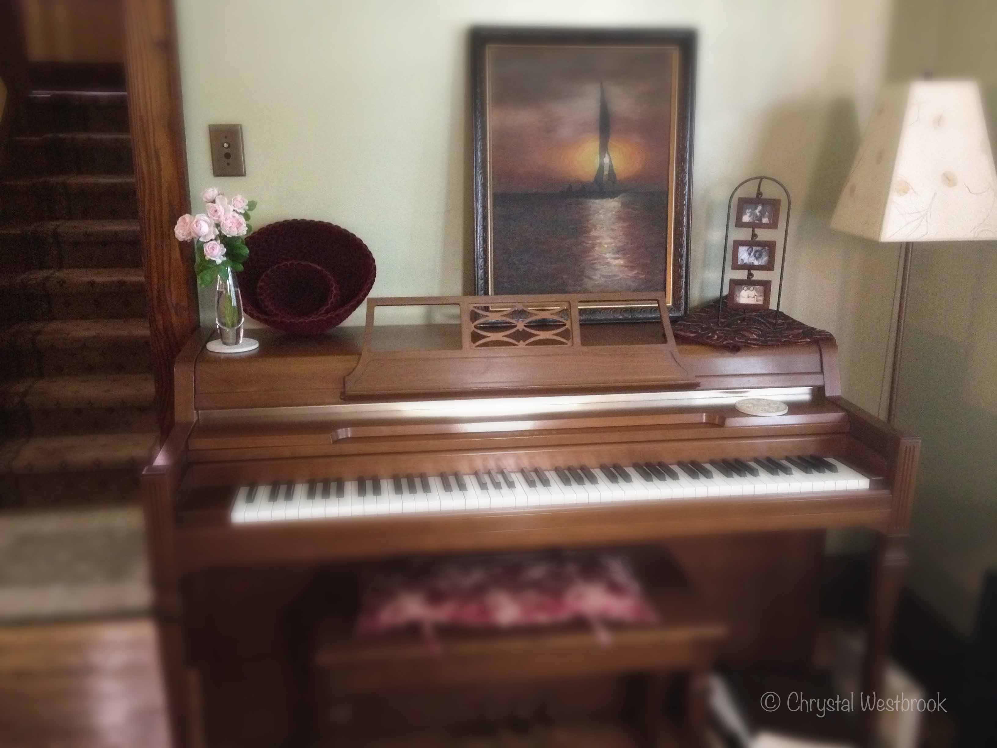 [IMAGE] spinet piano with a vase of roses