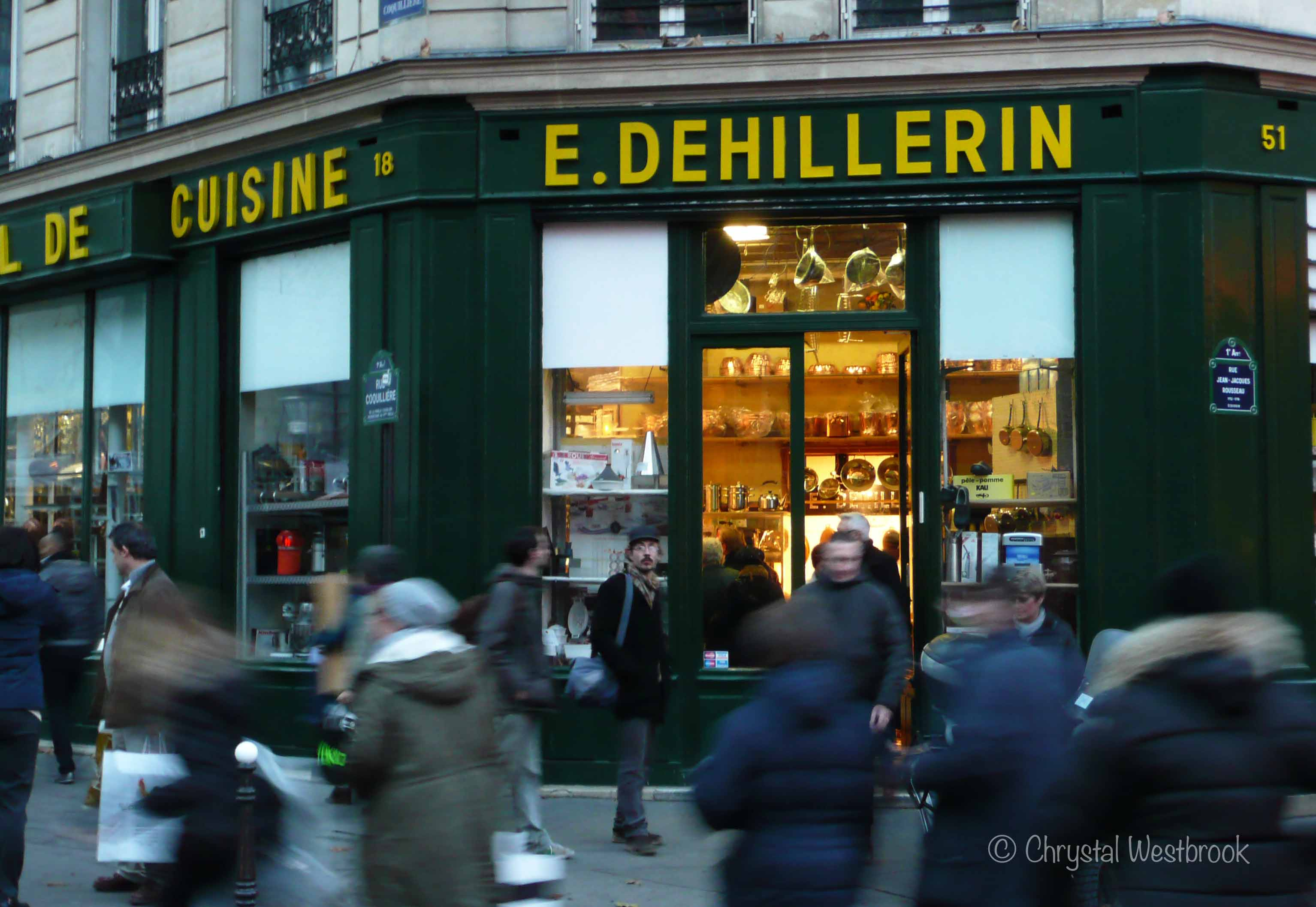 [IMAGE] Shoppers rushing by the well-lit entrance to a Parisian store